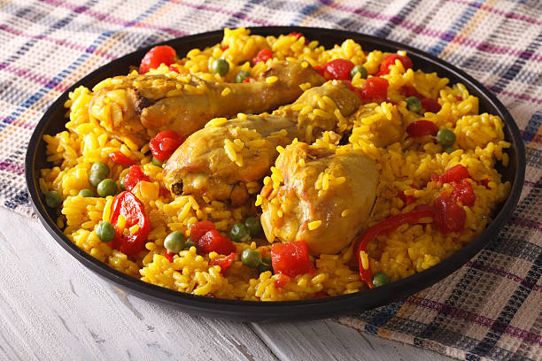 spanish paella with chicken closeup on a plate. horizontal - chicken rice stock photos and pictures