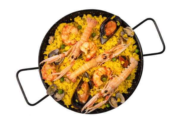 spanish seafood paella in paellera on white background - paella stock photos and pictures