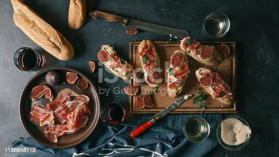 508216406 istock photo Spanish snacks and wine on a dark concrete background. tapas, pinchos, bruschetta of Delicious ham, jamon, baguette, figs, cheese and herbs on the dining table. 1186848113