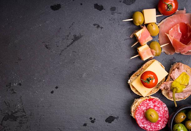las tapas españolas en un fondo negro stone - fuet sausages fotografías e imágenes de stock