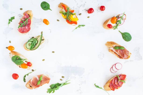 spanische tapas auf weißen tisch. flach legen, top aussicht - salami vorspeise stock-fotos und bilder