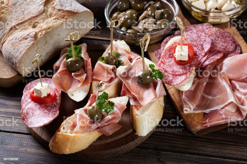 Spanish tapas with slices jamon serrano, salami, olives and cheese...