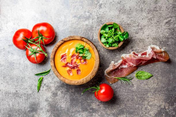 spanische tomatensuppe salmorejo serviert in olivenöl holzschale mit schinken jamon serrano auf stein hintergrund. ansicht von oben - kalte tomatensuppe stock-fotos und bilder