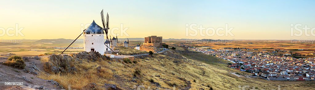 Spanish windmills and castle at sunset stock photo