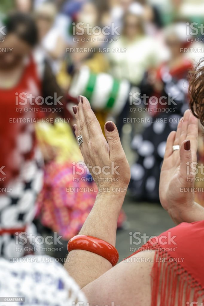 Spanish woman dressed in flamenco, dancing and clapping her hands at the Seville's April Fair. stock photo
