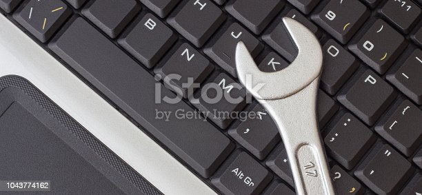 Spanner on the laptop keyboard, the concept of repairing machinery, close-up
