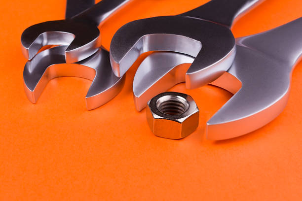 Spanners of different sizes arranged around a circle on a yellow background. stock photo