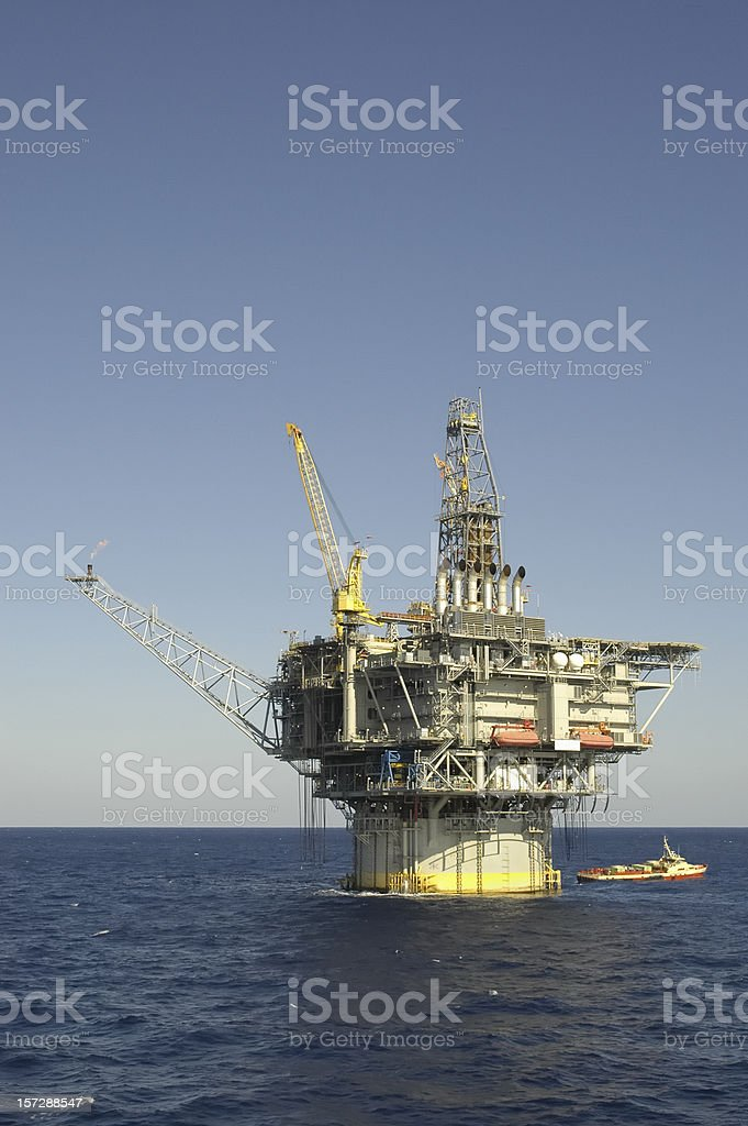 Spar production platform with flare. Oil rig and supply vessel royalty-free stock photo