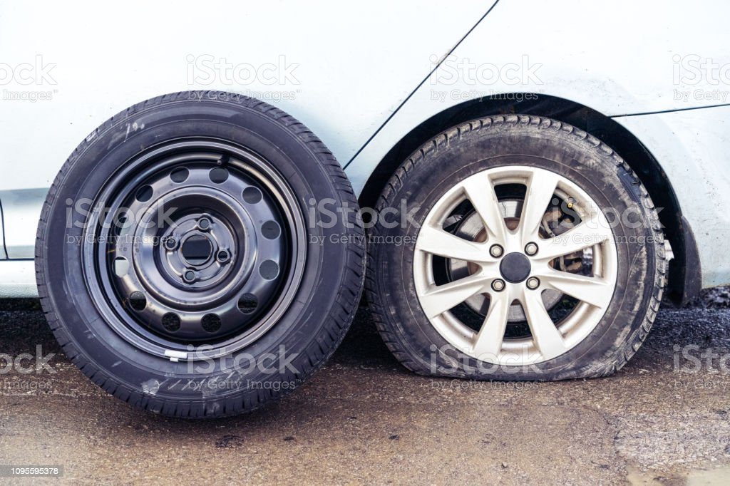 spare tire and flat tyre on roadon the background of the car. Car tire leak because of nail pounding. stock photo