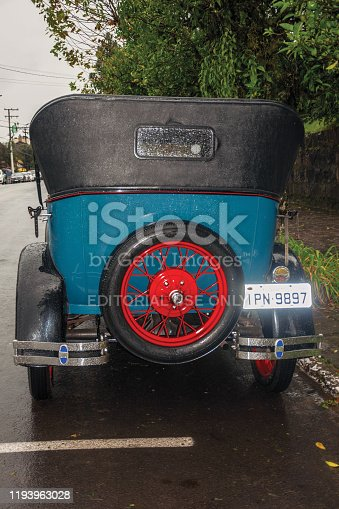 Gramado, Brazil - July 23, 2019. Detail of spare tire in the back of antique Ford 1929 car in perfect condition, on a rainy day in Canela. A charming small town very popular by its ecotourism.