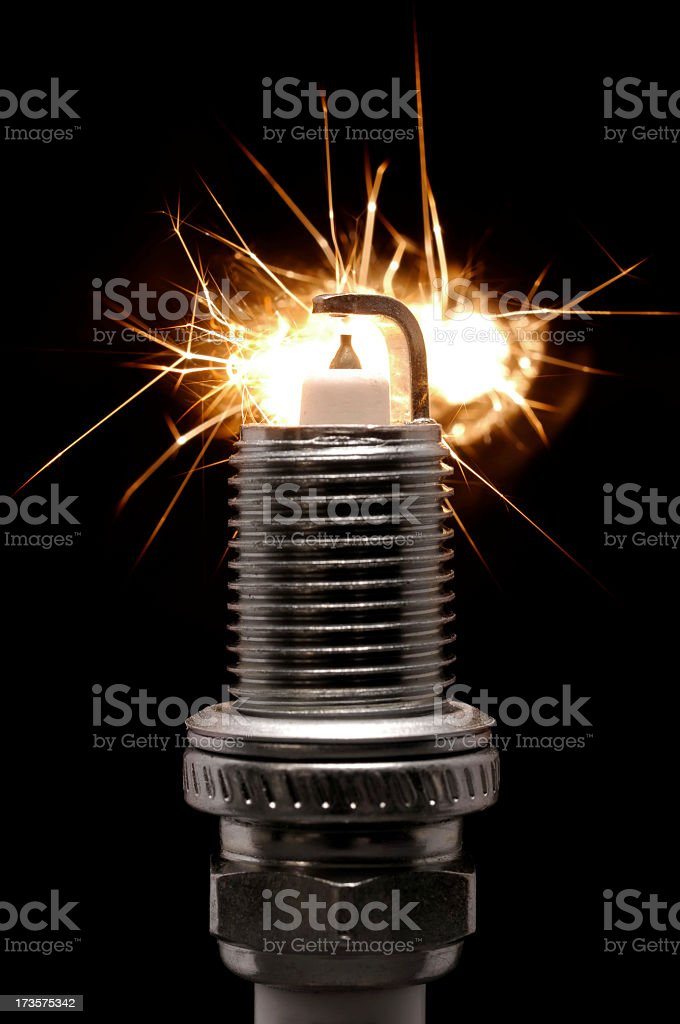 Spark plug with active sparks against a black background stock photo
