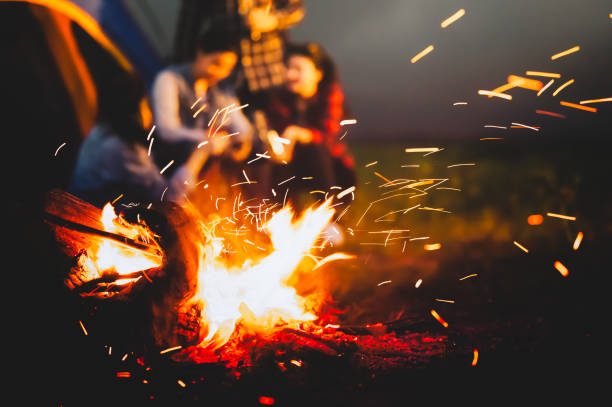 sparking bonfire with tourist people sit around bright bonfire near camping tent in forest in summer night background. group of student at outdoor fire fuel. travel  activity and long vacation weekend - falò spiaggia foto e immagini stock