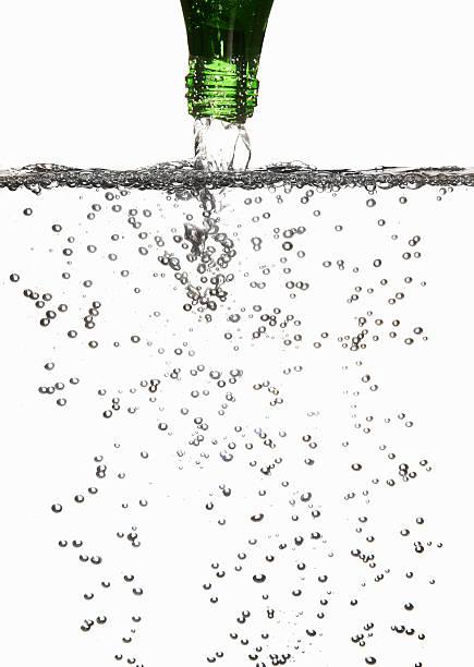 スパークリングウォーターに注ぐグラス - 炭酸飲料 ストックフォトと画像