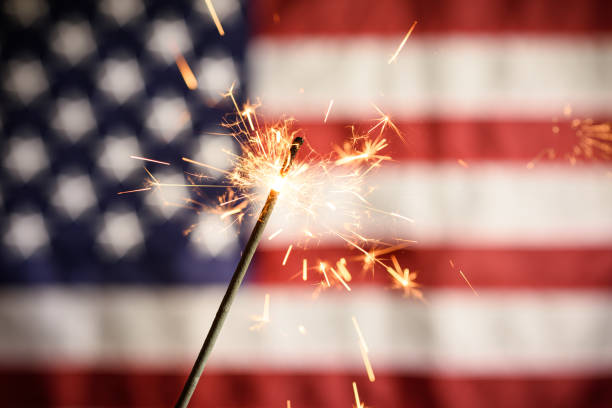 Sparkler Closeup With American Flag In Background. Celebrating 4th Of July Independence Day stock photo