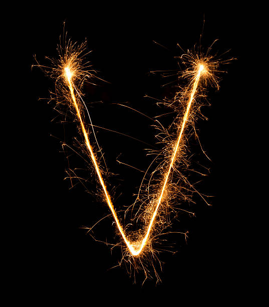 Sparkler firework light alphabet V at night stock photo