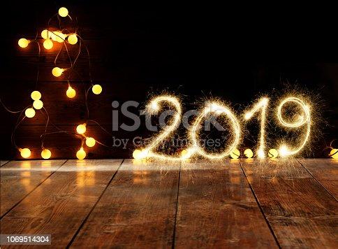 istock Sparkler Happy New Year 2019 With Defocused Lights On Wooden Floor 1069514304