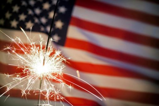 182764873 istock photo Sparkler Infront Of American Flag 187276797
