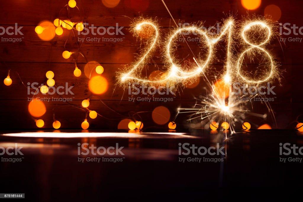 Wunderkerze Neujahr 2018 mit Feuerwerk auf Holzboden – Foto