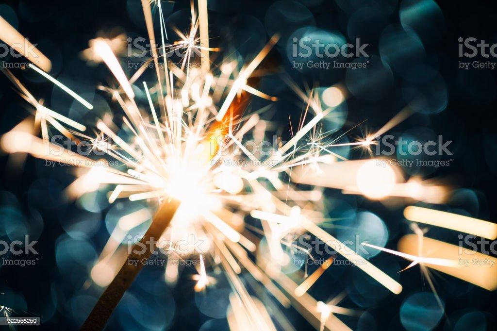 Sparkler on defocused Blue Background stock photo