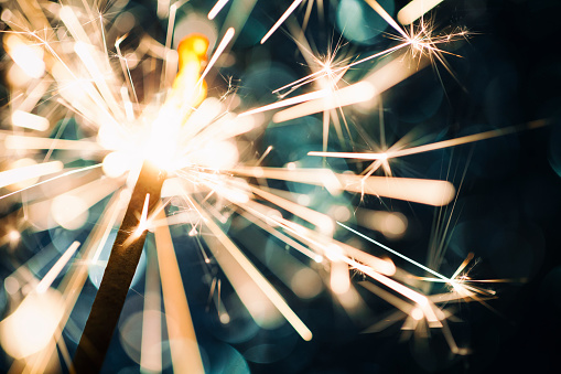 Sparkler On Defocused Blue Background Stock Photo - Download Image Now