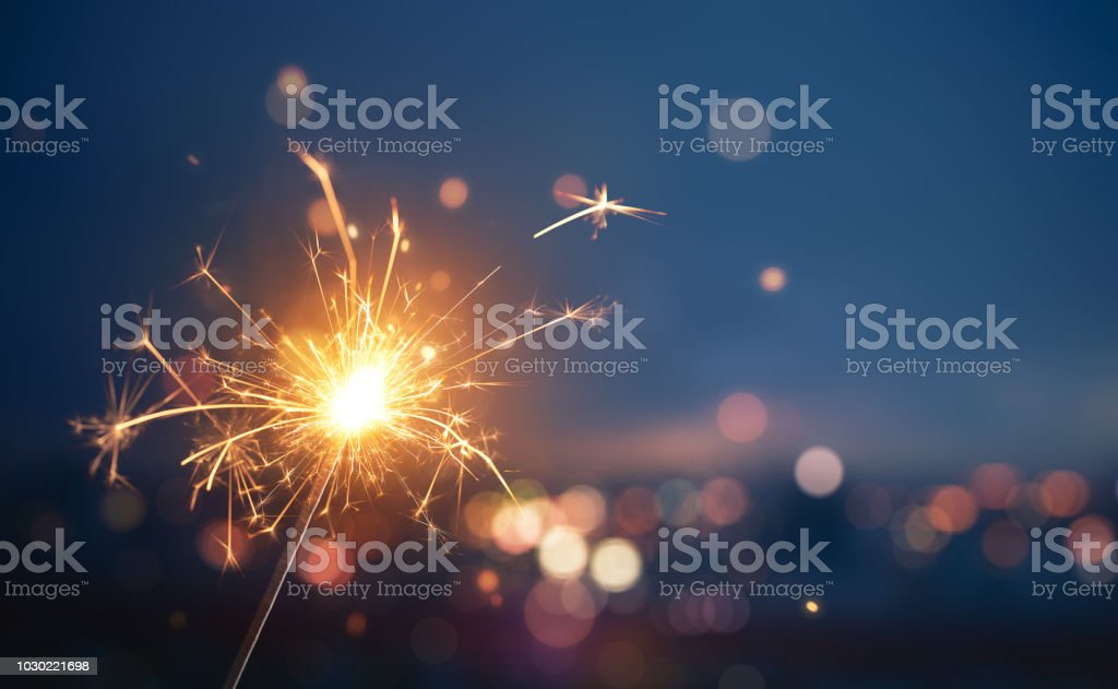 Sparkler with blurred busy city light background Sparkler with blurred busy city light background Abstract Stock Photo