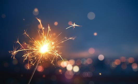 Sparkler With Blurred Busy City Light Background - Fotografias de stock e mais imagens de Abstrato