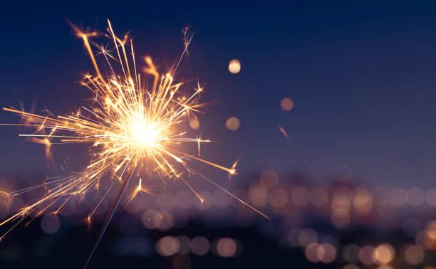sparkler com fundo borrado da luz da cidade, ano novo feliz - estrelinha - fotografias e filmes do acervo