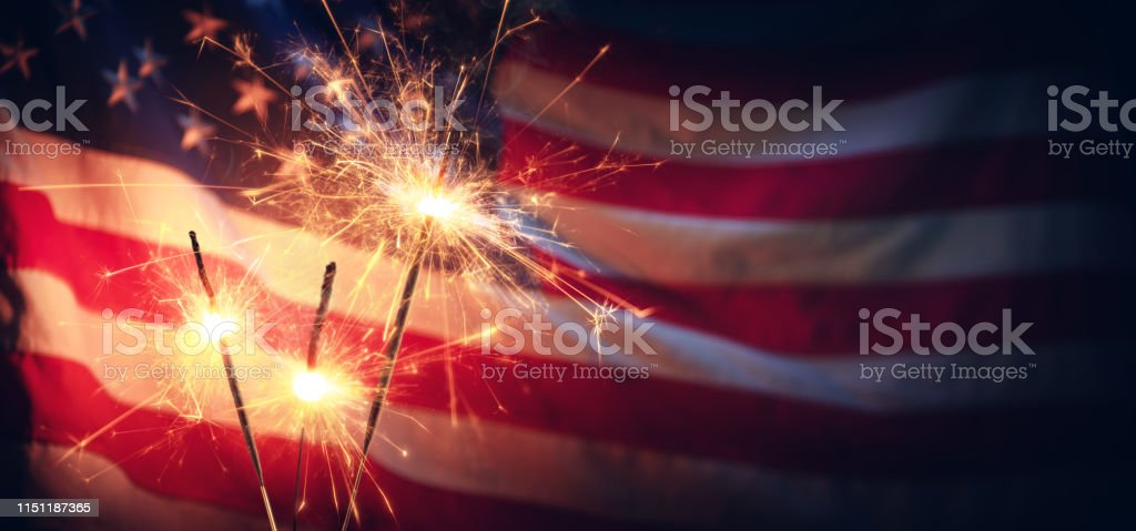 Sparklers And American Flag - Independence Day Vintage Celebration With Sparklers And Defocused American Flag - Independence Day American Culture Stock Photo