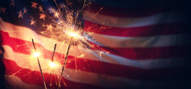 Sparklers And American Flag - Independence Day Vintage Celebration With Sparklers And Defocused American Flag - Independence Day independence day photos stock pictures, royalty-free photos & images