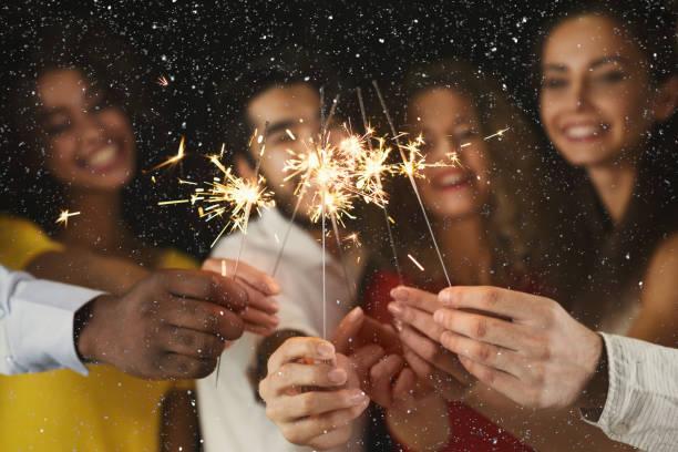 fondo de luces de bengala. jóvenes en la fiesta de celebración - año nuevo fotografías e imágenes de stock