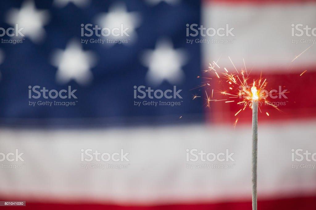 Sparklers burning against American flag background stock photo