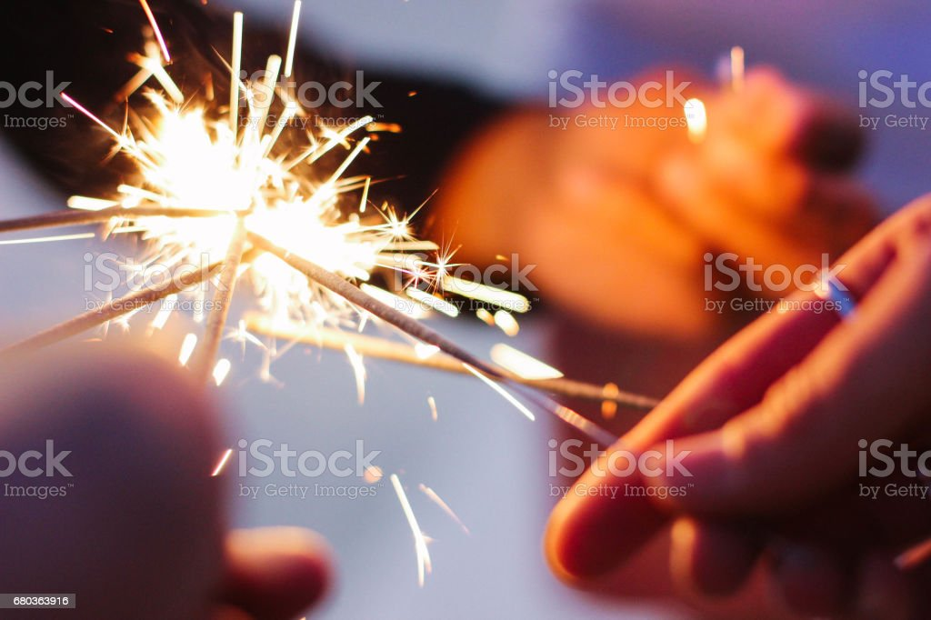 Sparklers in group of friends' hands stock photo
