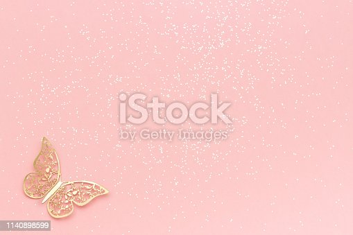 1040055260istockphoto Sparkles glitter and gold tracery butterfly on pink pastel trendy background. Festive background, template 1140898599