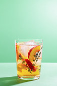 Sparkling cold brew peach tea with thyme in glass on green paper background close-up. Refreshing summer non-alcoholic drink concept