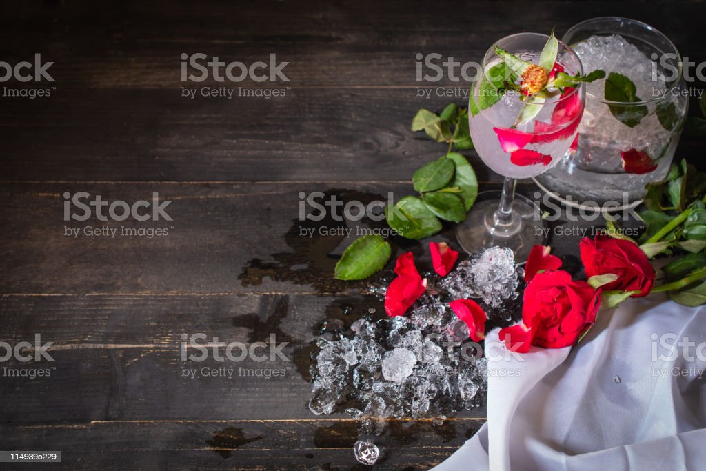 Sparkling cold water detox with rose and ice on the wood table there...