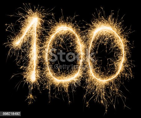 Birthday number 100 in gold sparklers on black background.