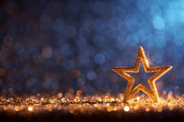 Sparkling Golden Christmas Star - Ornament Decoration Defocused Bokeh Background stock photo