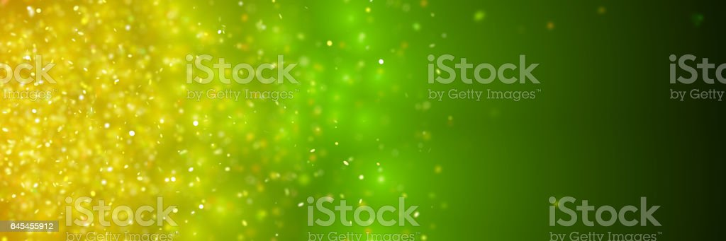 sparkling golden glitter in front of a dark green and yellow background stock photo