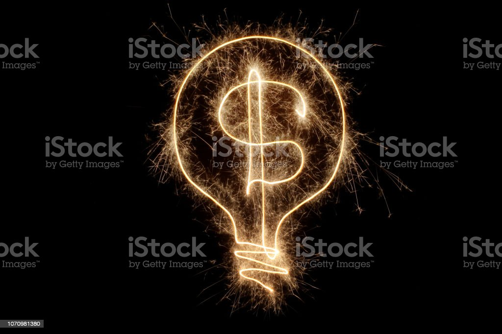 Light bulb with dollar sign made from sparkler on black background...