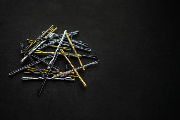glitzernde metall silber goldene und schwarze haarnadeln auf einem schwarzen hintergrund. ein haufen von haarnadeln für abend- und festliche frisuren. abends haar-accessoire, brautjungfer haarnadeln, vintage-stil - haarnadeln stock-fotos und bilder