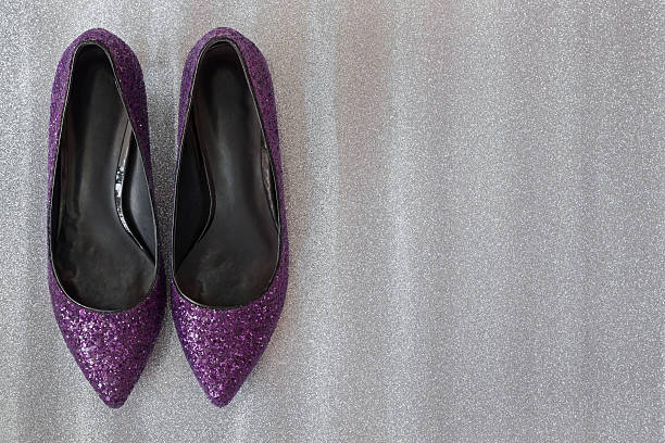 sparkling stylish purple magenta high heels on glittery silver background - flat shoe stock photos and pictures
