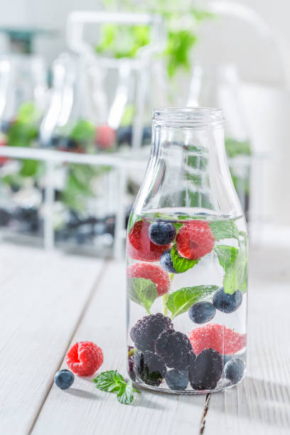 sparkling water in bottle with raspberries, blueberries and blackberries - baie eau photos et images de collection
