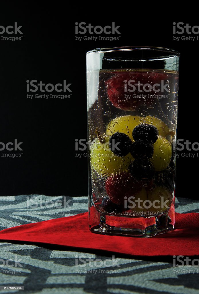 Sparkling water with fruit in a high glass stock photo