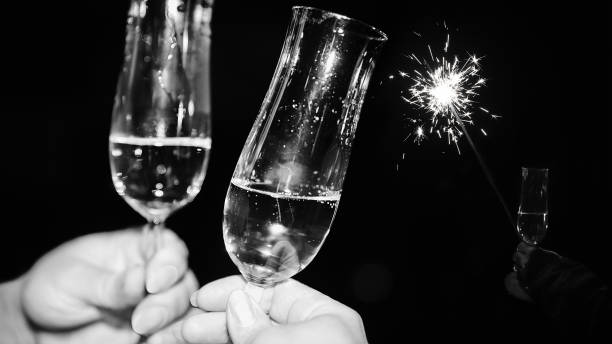 Sparkling wine with two champagne glasses and sparkler in background stock photo