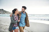 Shot of a young couple enjoying a stroll on the beach