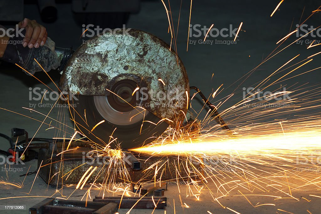 Sparks fly as a rotating wheel cuts through metal royalty-free stock photo