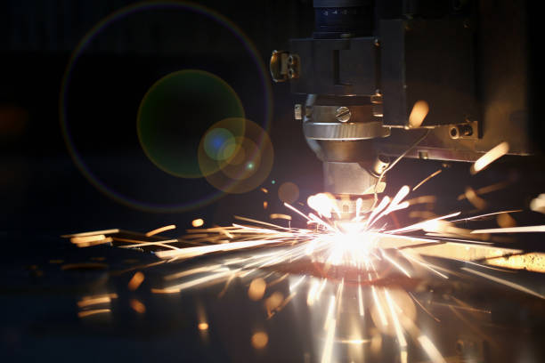 Sparks fly out machine head for metal processing Sparks fly out machine head for metal processing laser metal on metallurgical plant background. Manufacturing finished parts for automotive production concept metalwork stock pictures, royalty-free photos & images