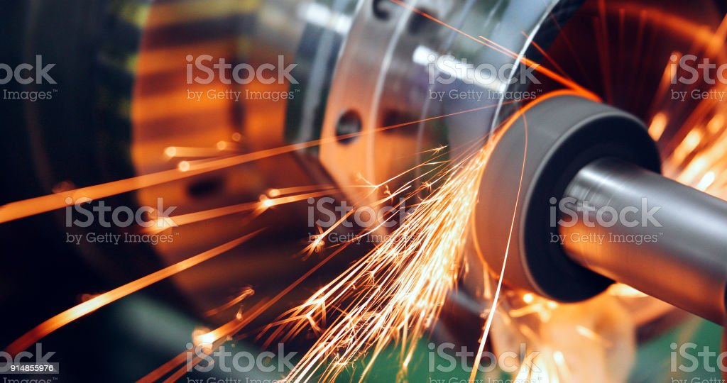 sparks flying while machine griding and finishing metal stock photo