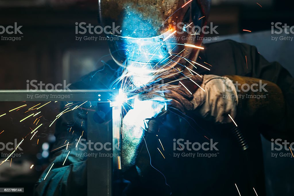sparks while welder uses torch to welding stock photo