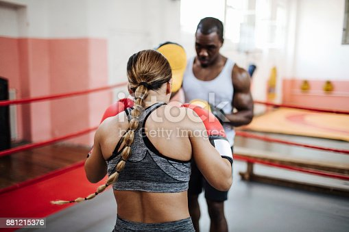 Young girl training at the gym with personal trainer